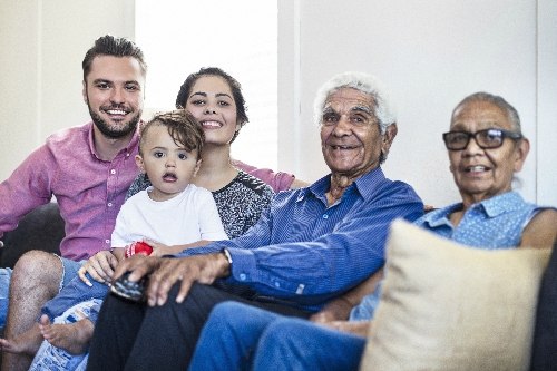 Different generations of a family sit together on a sofa, smiling at the camera